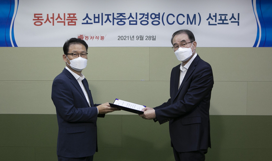 Lee Kwang-bok, Dongsuh Foods president, right, awards a certificate of appointment of the chief customer officer role to Park Young-soon, Dongsuh Foods associate vice president, at a proclamation ceremony held by Dongsuh Foods at its Seoul office in Mapo District, western Seoul, on Tuesday.