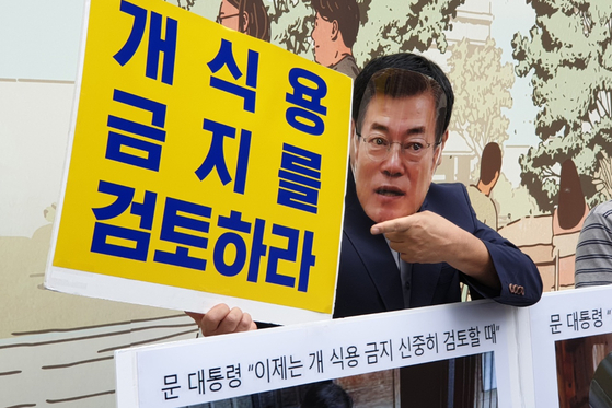 """Local animal rights activists hold a rally at the Gwanghwamun Square in central Seoul on Tuesday to call for the banning of dog meat consumption in the country. One activist, wearing a mask of President Moon Jae-in, is holding a sign that reads, """"Review banning dog meat consumption."""" [YONHAP]"""