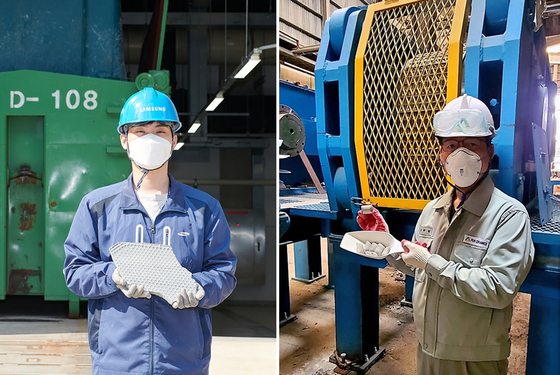 A Samsung Electronics employee, left, and a Pos Ceramics employee pose for a photo holding wastewater sludge and the fluorite alternative product that was made with it. [SAMSUNG ELECTRONICS]