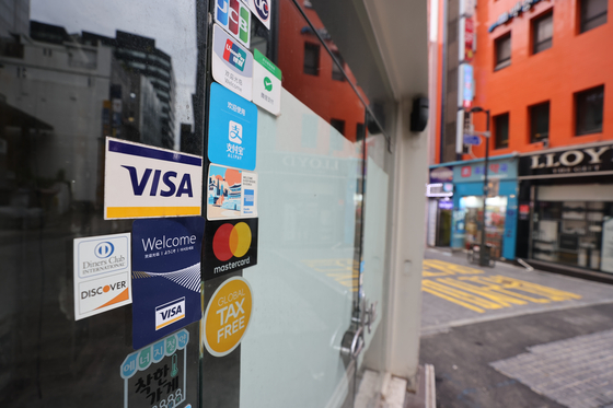 Credit card logo on a store that has been closed in Myeong-dong, Seoul on Monday. The government said a cash-back program whose goal is to help small stores that have been affected by the social distancing regulation will start Oct. 1. [YONHAP]