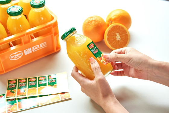 Del Monte's merchandise featuring six orange juice glass bottles and a plastic crate with the juice maker's logo. [LOTTE CHILSUNG BEVERAGE]