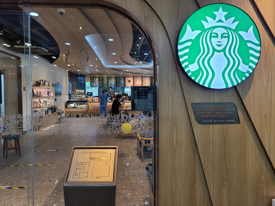 In front of a Starbucks coffee shop at Seoul National University Dental Hospital are a braille guide to the interior of the shop and a plaque that says a disabled person work there. [CHUNG HEE-YUN]