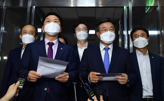 Kim Gi-hyeon, front left, floor leader of the opposition People Power Party, and Yoon Ho-joong, front right, floor leader of the ruling Democratic Party, hold a joint press conference at the National Assembly on Wednesday to announce that they agreed to establish a special committee to discuss a media reform bill. The ruling and opposition leaders announced that the special committee will work on the media revision bill until Dec. 31, 2021, and will consist of 18 members - nine members each from the ruling and opposition parties. [LIM HYUN-DONG]