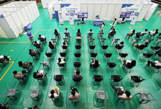 People wait to receive jabs at a Covid-19 vaccination center in Dongdaemun District, eastern Seoul, on Wednesday. Unvaccinated people can reserve for a shot until 6 p.m. Thursday on the Covid-19 reservation website (https://ncvr.kdca.go.kr). [YONHAP]