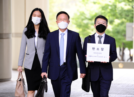 Lawyer Kang Sin-seob of Shin & Kim LLC, center, the attorney for SK Broadband heads to the Seoul High Court to file a counter-suit against Netflix on Thursday with his team. [SK BROADBAND]