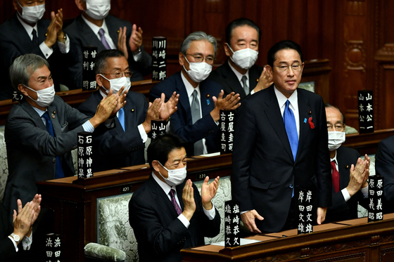 Fumio Kishida, standing, receives applause after he is elected as Japan's new prime minister at the lower house of the Diet in Tokyo Friday. Korean President Moon Jae-in sent a congratulatory letter to Kishida the same day. [AFP/YONHAP]