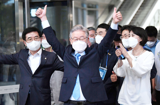 """Gyeonggi Gov. Lee Jae-myung gives two thumbs-up to his supporters as he exits Songdo Convensia in Incheon after winning a victory in the party's second ″super week"""" Sunday, bringing him closer to becoming the ruling Democratic Party's presidential candidate. [JOINT PRESS CORPS]"""