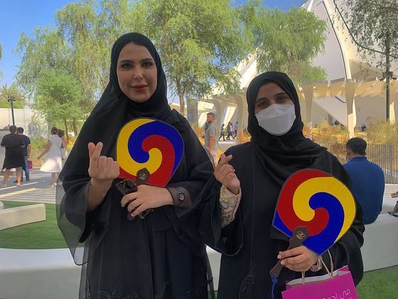 Visitors to the Korea Pavilion, Norah Awad from Saudi Arabia, left, and Wasmeya Alrashdi from Abu Dhabi, pose for a photo holding fans from the pavilion. They told the Korea JoongAng Daily that they especially liked the Korean food. [SARAH CHEA]