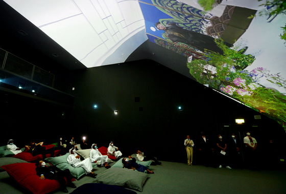 People are lying down in the Vertical Cinema zone of the Korea Pavilion, which has a mega-sized screen and allows people to watch videos. [KOREA TRADE-INVESTMENT PROMOTION AGENCY]