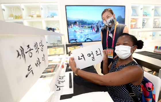 A visitor to the Korea Pavilion poses for a photo after learning about Korean calligraphy on Oct. 1. [KOREA TRADE-INVESTMENT PROMOTION AGENCY]