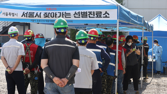 Construction workers line up to take virus tests at a Covid-19 screening center installed at a construction site in Gangnam District, southern Seoul on Friday. [YONHAP]