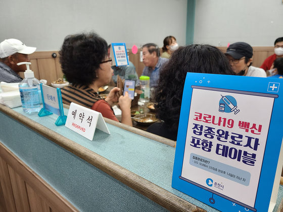 """Six fully vaccinated people dine together Sunday at a restaurant in Chuncheon, Gangwon, at a table with a tabletop sign that reads """"Table with fully vaccinated people."""" The Chuncheon city government is currently distributing fully vaccinated tabletop signs to the city's restaurants in order to prevent false accusations of a violation of social distancing rules for group customers. [YONHAP]"""