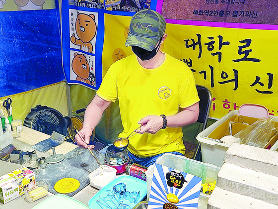 """An Sae-hwan, 37, is making dalgona (a thinly spread Korean sugar candy with a stamped outline of a random shape) inside his 2-square-meter (22-square-foot) candy stand near Hyehwa Station in eastern Seoul on Monday evening. His candy stand distributed the candies to the production team of the viral Netflix Korea original series, """"Squid Game."""" [JOONGANG ILBO]"""