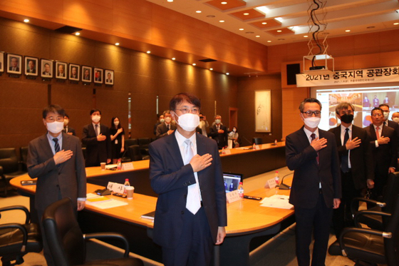Korean diplomats from the embassy and consulates in China, including Korean Ambassador to China Jang Ha-sung, center front, salute the Korean flag at the beginning of a meeting in Beijing on July 9. [YONHAP]