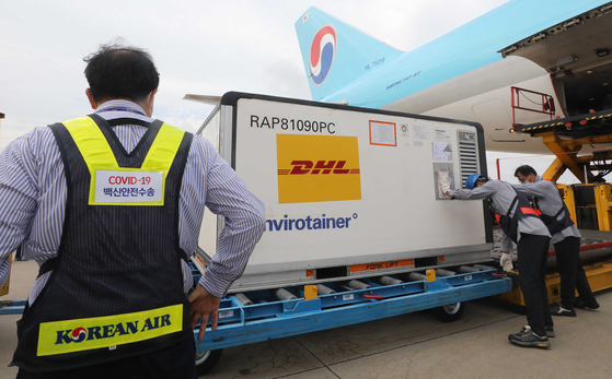 Workers unload boxes carrying some 94,000 doses of Pfizer's Covid-19 vaccine at Incheon International Airport on Thursday. This is the first batch of a total of 1 million doses of Pfizer vaccines that Britain agreed to send to Korea under a bilateral vaccine swap deal. [YONHAP]