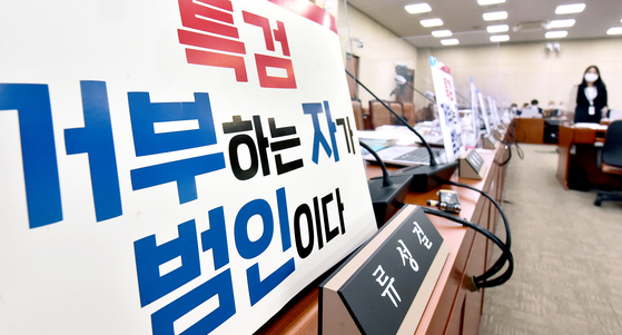 A different placard placed in front of the seat of opposition People Power Party lawmaker Yoo Sung-kull's seat before the Strategy and Finance Committee's meeting on Tuesday lambasts those who reject the proposal for an independent counsel probe into the development. Gyeonggi Gov. Lee Jae-myung has opposed such a probe. [LIM HYUN-DONG]