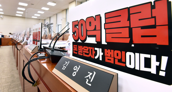 A sign placed in front of the seat of ruling Democratic Party lawmaker Kim Young-jin's seat on the Strategy and Finance Committee meeting room of the National Assembly on Tuesday describes those who received profits from the Daejang-dong development as criminals. [LIM HYUN-DONG]