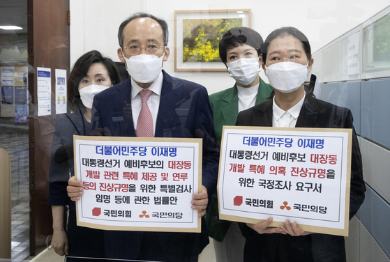 From left: People Power Party lawmakers Jun Ju-hyae, Choo Kyung-ho, Kim Eun-hye and People's Party lawmaker Kwon Eun-hee hold placards at the National Assembly on Thursday morning as they submit a proposal to create a parliamentary probe into Gyeonggi Governor Lee Jae-myung's connection to the Daejang-dong development project. [LIM HYUN-DONG]