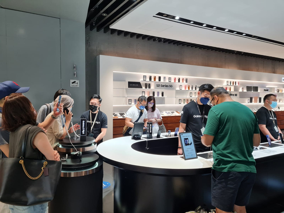People browse Samsung Electronics' Galaxy Z Flip 3 and Z Fold 3 at the company's experience store in Singapore. [SAMSUNG ELECTRONICS]
