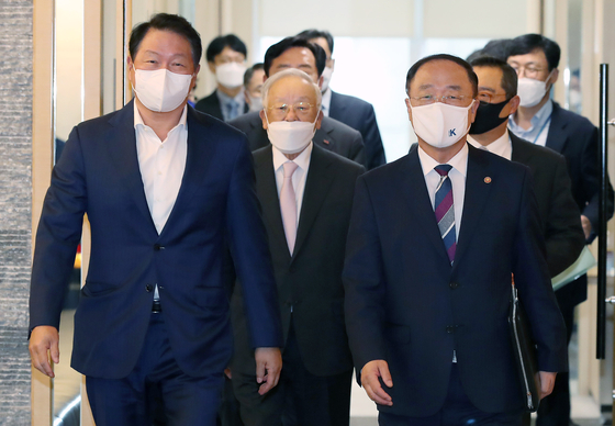 Chey Tae-won, chairman of the Korea Chamber of Commerce and Industry (KCCI), left, enters a conference room at the KCCI in central Seoul with Finance Minister Hong Nam Ki on Oct. 8. [YONHAP]