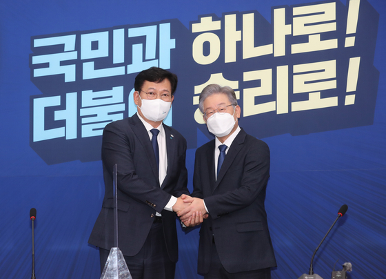 Song Young-gil, chairman of the ruling Democratic Party (DP), left, and Gyeonggi Gov. Lee Jae-myung, the DP's presidential candidate, shake hands at the National Assembly in western Seoul Monday. [YONHAP]