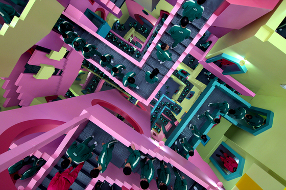This pink stairway maze, which players walk past to get to a new game, gives ″Alice in Wonderland″ vibes. Chae explains that it follows the general theme of confusion and chaos among the players. [NETFLIX]