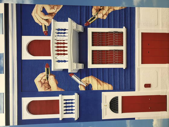 The original red, white and blue two-story building painted with four hands holding tubes of red lipstick of the Toiletpaper headquarters in Milan [SHIN MIN-HEE]