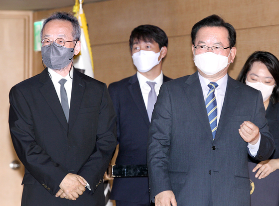 Prime Minister Kim Boo-kyum, right, and Choe Jae-chun, distinguished professor of EcoScience at Ewha Womans University, left, enter the inaugural meeting of a government-private sector committee at the government complex in Seoul on Wednesday. [NEWS1]