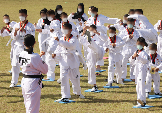 """Children of Afghan """"special contributors"""" evacuated from Kabul in August learn taekwondo at the National Human Resources Development Institute in Jincheon County, North Chungcheong, on Wednesday. [JOINT PRESS CORPS]"""