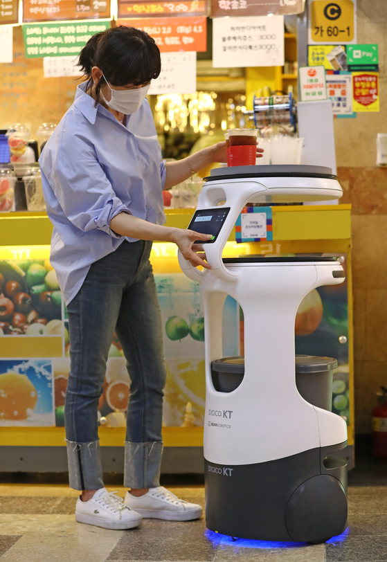 A robot delivers coffee at a ceremony to kick off the AI 5G-based Service Robot Project, held in the underground shopping area of Jungangno Station in Daejeon, on Wednesday. As part of the project, two delivery robots will deliver coffee in the shopping area starting early next year. Other robots will be used to disinfect and patrol the area starting at the end of this year. [YONHAP]