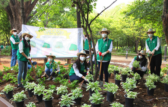 Starbucks baristas pose for a photo after planting trees and plants at a 300-pyeong (992-square-meter) space in Seoul Forest in Seongsu-dong, eastern Seoul, on Oct. 5. The company held a ″Cup a Tree″ event in April, promising to create a garden and forest area of 1 pyeong for every 10 photos posted with the hashtag #CupATree. [STARBUCKS COFFEE KOREA]