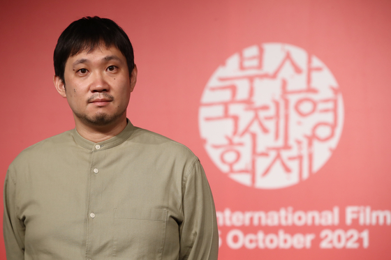 Japanese filmmaker Ryusuke Hamaguchi poses for photos after a press event at KNN Theater in Busan on Oct. 8. [YONHAP]