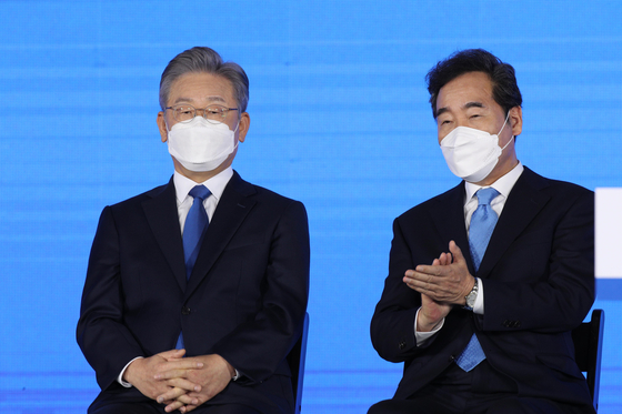 Presidential hopefuls Lee Jae-myung, left, and Lee Nak-yon listen to the results of the Democratic Party's (DP) primary race Sunday in Songpa District, eastern Seoul. Gyeonggi Gov. Lee Jae-myung won a narrow majority and was nominated as the DP presidential candidate. [JOINT PRESS CORPS]