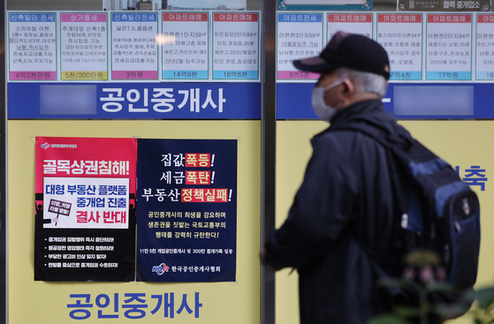 A notice posted in front of a real estate agency in Seoul on Tuesday criticizes the government's decision to lower commissions. Starting Tuesday, the new lowered rates will be applied. The rate cut is steeper for apartments valued 900 million won or above. Under the new system, the maximum commission on a 1-billion-won sale will be lowered from 9 million won to 5 million won. For a 1-billion-won jeonse, the commission will drop from 8 million won to 4 million won. Commissions have spiked recently as housing prices have soared. [YONHAP]