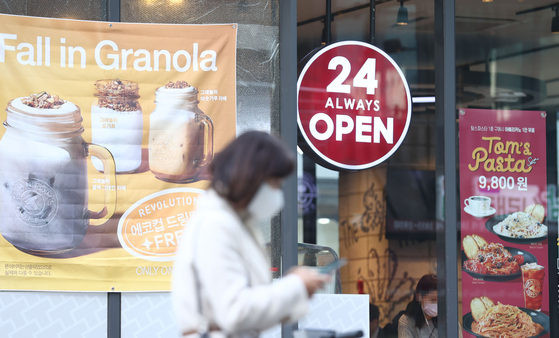 """A sign saying """"24 Hours Always Open"""" hangs in front of a cafe in Gangnam District, southern Seoul, on Monday. The government announced a draft for the """"With Corona"""" scheme that will allow restaurants and bars to stay open 24 hours a day. [YONHAP]"""