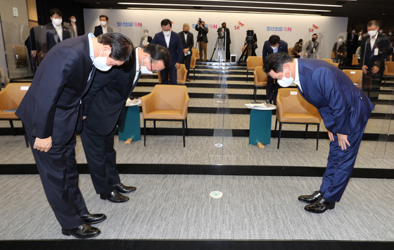 Front from left: Employment and Labor Minister An Kyung-duk, Prime Minister Kim Boo-kyum and SK Group Chairman Chey Tae-won bow to each other at a meeting held at the SK hynix R&D Center in Icheon, Gyeonggi, on Monday. Chey vowed to add 27,000 jobs within the next three years, 9,000 more than the company's original plan. [YONHAP]