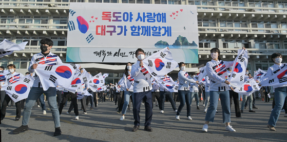In celebration of Dokdo Day on Monday, Daegu mayor Kwon Young-jin, along with 60 officials and staff members from Daegu Metropolitan Government and North Gyeongsang Provincial Government, perform a flash mob while holding Korean flags in front of Daegu City Hall. This year's Dokdo Day commemorates the 121st year since King Gojong, Korea's last king, declared sovereignty over the Dokdo islets on Oct. 25, 1900. [YONHAP]