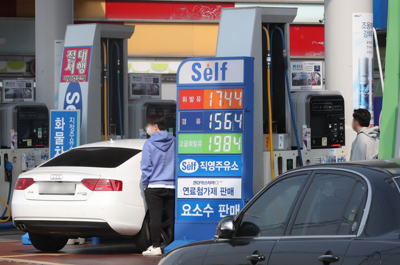 A customer filling up at a gas station in Seoul on Tuesday. Starting Dec. 12 fuel prices will be cut as the government decided to lower 20 percent on fuel taxes. [YONHAP]