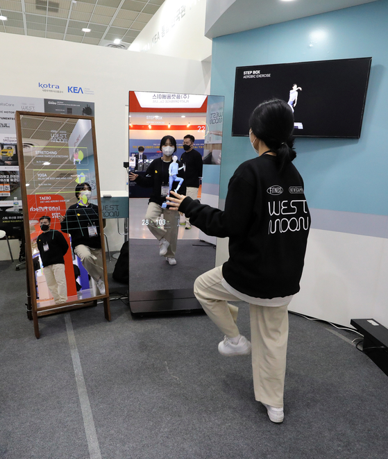 An employee of West Moon, a digital health care company, demonstrates a display that gives a workout regime during the Korea Electronics Show on Tuesday at Coex in Gangnam District, southern Seoul. Some 400 electronics companies including Samsung Electronics and LG Electronics are participating in the country's biggest electronics event that runs through Oct. 29. [NEWS1]