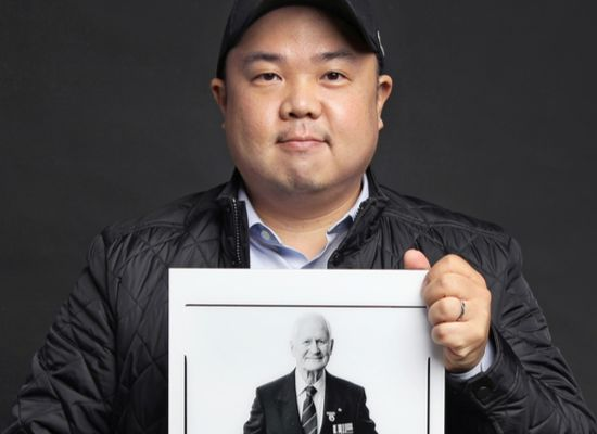 Photographer Rami Hyun, who's been taking pictures of foreign Korean War veterans since 2017, poses with one of his works — a picture of British veteran John Bowler — after an interview with the Korea JoongAng Daily at a studio in Gwanak District in southern Seoul. [PARK SANG-MOON]